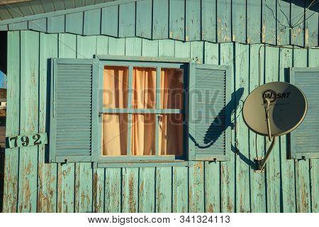 Cambara Do Sul, Brazil - July 16, 2019. Modern Satellite Dish And Open Window In Old Worn Wooden Hou