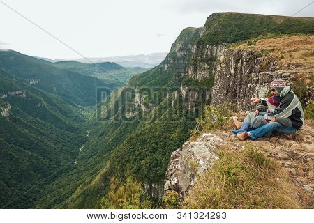 Cambara Do Sul, Brazil, July 17, 2019. People On Steep Rocky Cliffs In Fortaleza Canyon With Fog Com