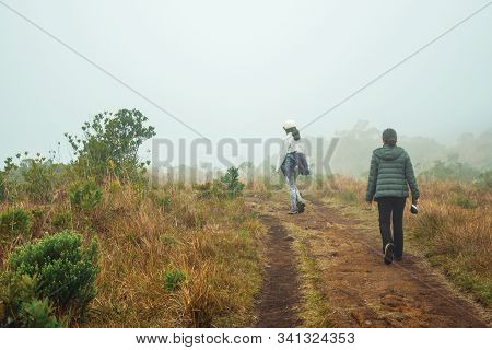 Cambara Do Sul - Brazil, July 18, 2019. People On Dirt Pathway Amid Dry Bushes And Mist At Serra Ger