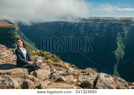Cambara Do Sul, Brazil - July 18, 2019. Smiling Woman Next To The Edge Of Rocky Cliff With Mist At F