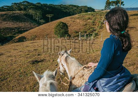 Cambara Do Sul, Brazil - July 18, 2019. Girl Riding Horse In A Landscape Of Rural Lowlands With Hill