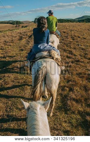 Cambara Do Sul, Brazil - July 18, 2019. Girl And Man Riding Horse In A Landscape Of Rural Lowlands C