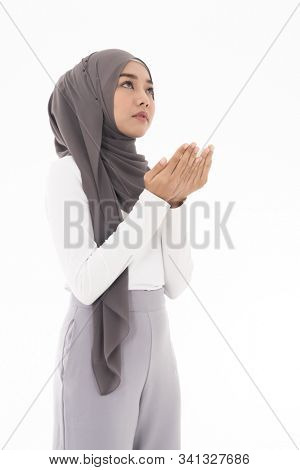 Young Adult Muslim Woman girl making Duas for Muslim god blessing prayer. Studio shot of woman isolated on white background