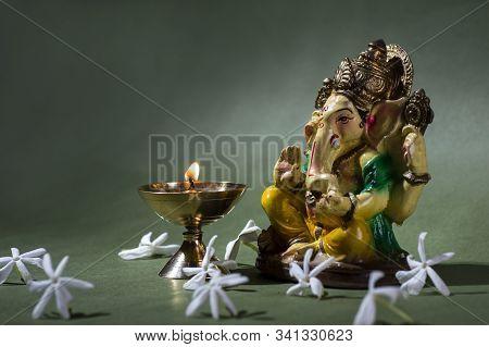Hindu God Ganesha. Ganesha Idol. A Colorful Statue Of Ganesha Idol On Dark Background. Space For Tex