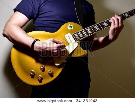 Man Playing A Golden Electric Guitar. Hands And Strings Closeup.