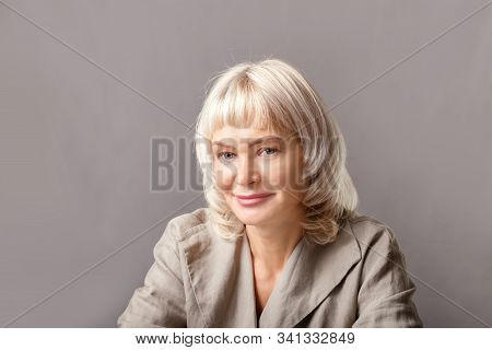 Portrait Of Older  Business Woman Smiling By Grey Wall.