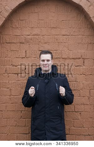 A Young Man In A Black Jacket Poses On A Background Of A Brown Brick Wall. Holds Hands In Front Of H