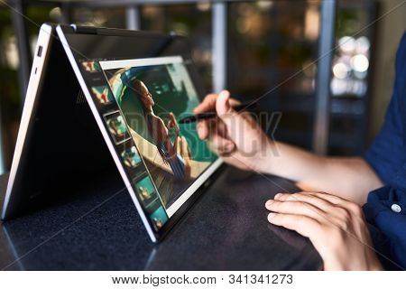 Freelancer Retoucher Man Works On Convertible Laptop Computer With Photo Editing Software Using Styl