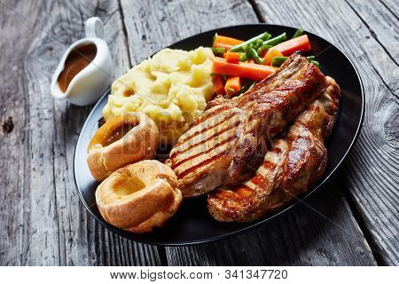 Close-up Of Traditional Sunday Roast With Grilled Pork Chops On  Bones, Mashed Potatoes, Green Beans