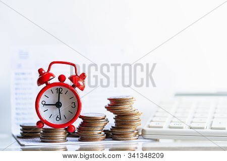 Red Alarm Clock On Stack Of Coins In Concept Of Savings And Money Growing. Business Investment Growt