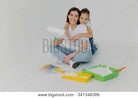 Indoor Shot Of Happy Woman Gets Warm Hug From Lovely Daughter, Pose Together In Empty Room, Choose B