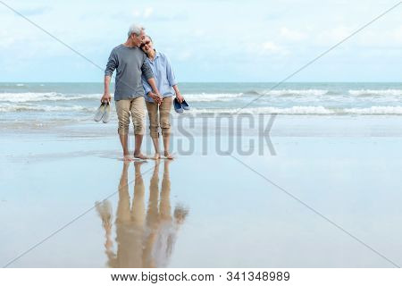 Lifestyle Asian Senior Couple Happy Walking Hug And Relax On The Beach.  Tourism Elderly Family Trav