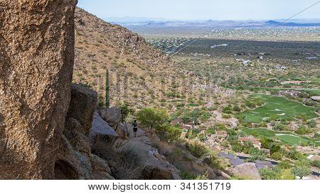 Hiker Running Down Pinnacle Peak Trail In North  Scottsdale, Az With Home And Golf Course In Backgro