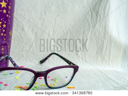 Coming Into The Frame Is A Pair Of Glasses Representing Vision And A Cheerful Purple And Gold Cup Re