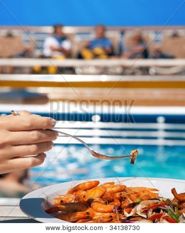 woman on deck eating seafood cocktail with fork near pool