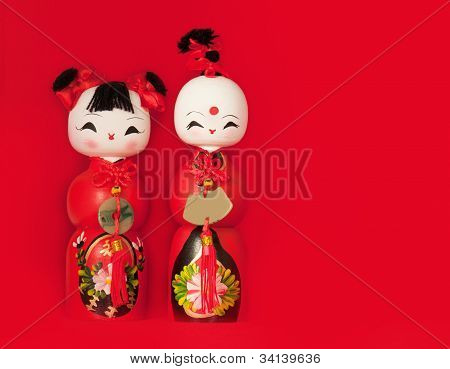 Two traditional wooden Chinese dolls isolated against red background
