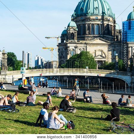 BERLIN, GERMANY - MAY 25, 2018: People relaxing at the James-Simon Park in Berlin, Germany, with the Spree River and the Berliner Dom, the Cathedral of Berlin, in the background