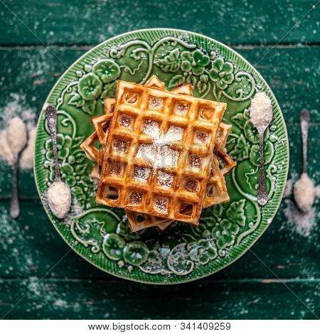 Almond Waffles On A Green Decorated Plate Sprinkled With Almond Meal