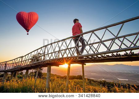 Silhouetted Of Asian Man Standing On Bamboo Bridge With Red Hot Air Balloon In The Shape Of A Heart