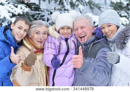 Happy Family In Snow Covered Winter Forest With Thumbs Up
