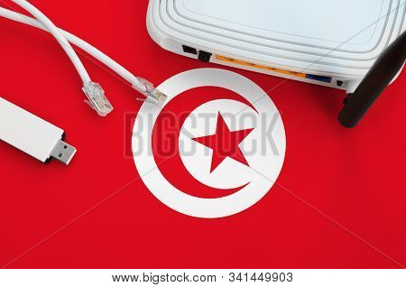 Tunisia Flag Depicted On Table With Internet Rj45 Cable, Wireless Usb Wifi Adapter And Router. Inter