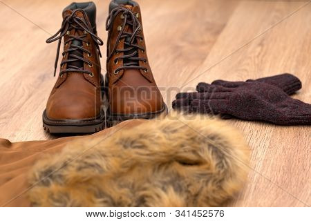 Warm Winter Clothes, Mens Boot, Coat And Gloves On Wooden Floor