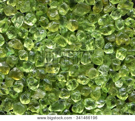 Olivine gemstone also called Peridot on old wooden background. poster