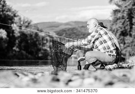 Sharing His Secrets. Experienced Fisherman Show Tips To Son. Beautiful Evening Riverside. Men Rivers
