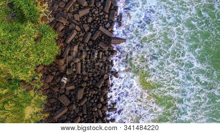 Top down aerial view of person sitting on rocks by the ocean at Burleigh headland, Gold Coast.