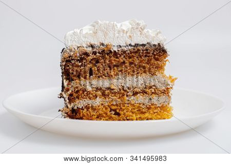 A Large Piece Of Biscuit Cake On A White Plate. Eating Sugary Food Rich On Carbs Concept