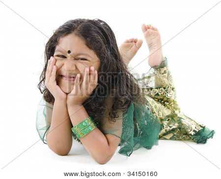 Young little Asian Indian girl smiling and lying on white background
