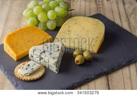 Cheese Board With Three Cheeses, Gouda With Pimento, Gouda With Cumin Seeds And Roquefort Blue Chees