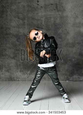 Cheerful Frolic Kid Girl In Leather Jacket, Stylish Jeans And Sunglasses Is Having Fun Playing Danci