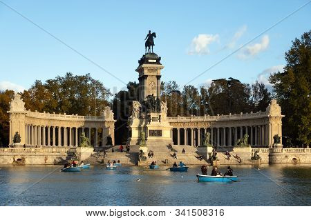 Madrid, Spain - December, 2019: People Enjoying Time On The Row Boats Swimming Around Monument To Al