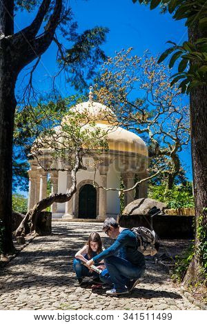 Sintra, Portugal - May, 2018: Father And Daugther Looking At A Map Of The Gardens Of Pena Park At Th