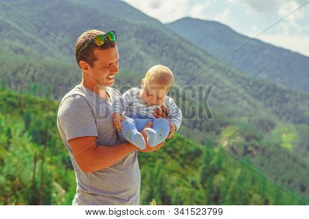 Dad Holding A Baby In His Arms Against The Mountains