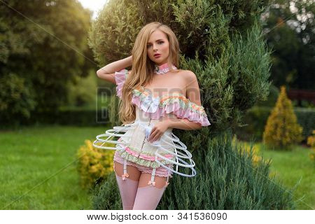 Sexy Blonde Woman Wearing Beautiful Lingerie With Stockings And Corset, Walking In Garden Labyrinth,