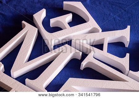 White Letters Cut Out Of Foam Without Painting On A Blue Background. Blank For Decoration, Logo Maki
