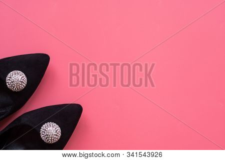 Close-up Black Suede Womens Shoes With Rhinestone Embellishments On A Pink Background