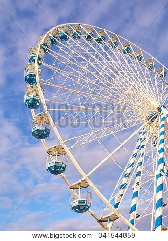 A Metallic Ferris Wheel With A Cloudy Sky In The Background.