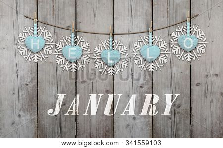 Hello January Written On Hanging Ice Blue Hearts And White Wooden Snowflakes On Weathered Planks Bac