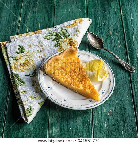Slice Of Lemon Tart Served On A Small Rustic Plate