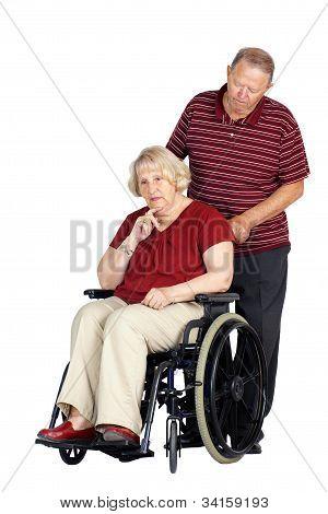 Elderly or senior couple with man caring for his wife in a wheelchair looking sad or depressed studio shot isolated over white background. poster