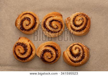 Freshly Baked Cinnamon Buns Rolls On A Tray Lined With Baking Parchment Paper