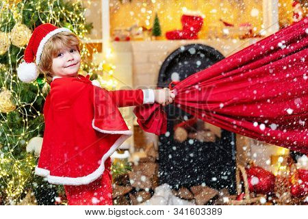 Santa Claus Helper Carrying Big Bag Full Of Gifts. Santa Helper Holding A Red Bag With Presents. Dre