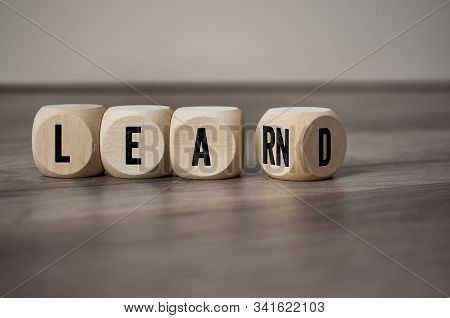 Cubes And Dice With The Word Learn And Lead On Wooden Background