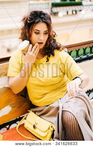 Beautiful Cheerful Curly Woman In A Bright Yellow Sweater With A Handbag