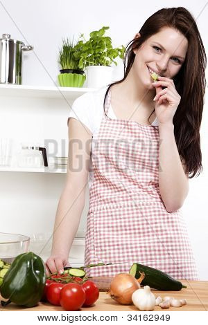 woman in a kitchen nibbling on a cucumber
