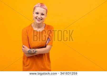 Unusual Pretty Female With Short Pink Hair And Tattoo Smiles Isolated On Orange Background