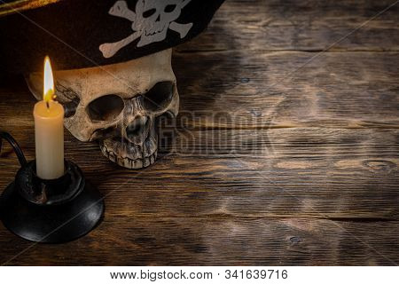 Pirate Hat On Human Skull And Burning Candle On Wooden Desk Background With Copy Space.